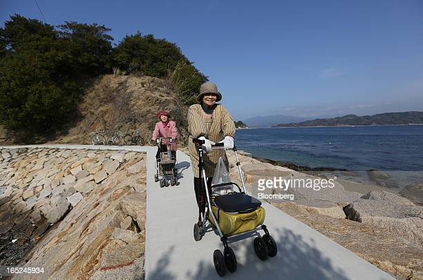 Tsutako Hashimoto right and Kiku Sakakibara walk with their strollers along the coastline on Gogo Island in Matsuyama Ehime Prefecture Japan on...