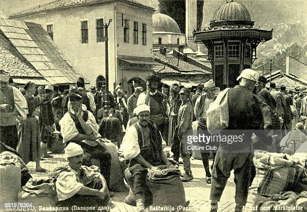 Tthe market in Sarajevo Serbia C 1930s Men wearing traditional costume with large sacks of produce One woman amongst the crowd of men
