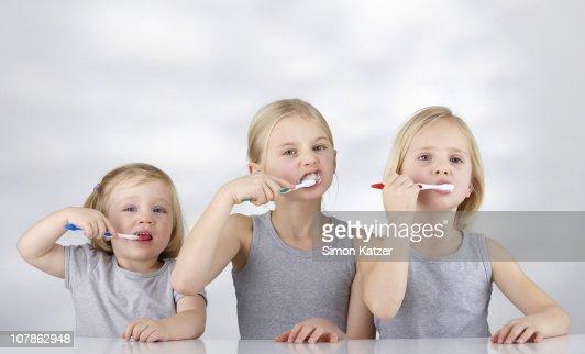 Tthree children brushing their teeth : Stock Photo