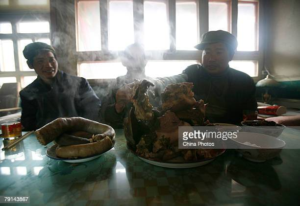 Tu ethnic villagers eat cooked pork in a villager's home at the Wushi Village on January 21 2008 in Huzhu County of Qinghai Province China In...