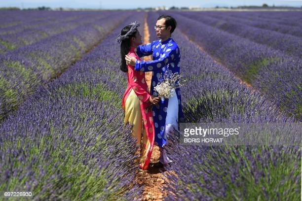 TOPSHOT Tu Lam Thanh and Nguyen Thi Tuyet Hai from Vietnam wearing traditional Vietnamese wedding clothes pose in a lavender field in Valensole...