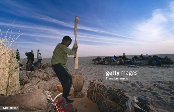 Tuareg boy pounding millet in mortar at Tenere desert camp.