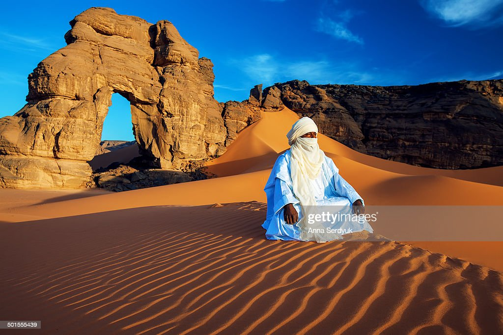 CONTENT] Tuareg is a nation living in the Sahara desert This man dressed in traditional festive clothes watching the sunrise while sitting at a huge...