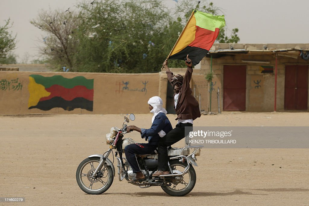 A Tuareg man waves the flag of the National Movement for the Liberation of Azawad during a demonstration in support of the MLNA on July 28 2013 in...