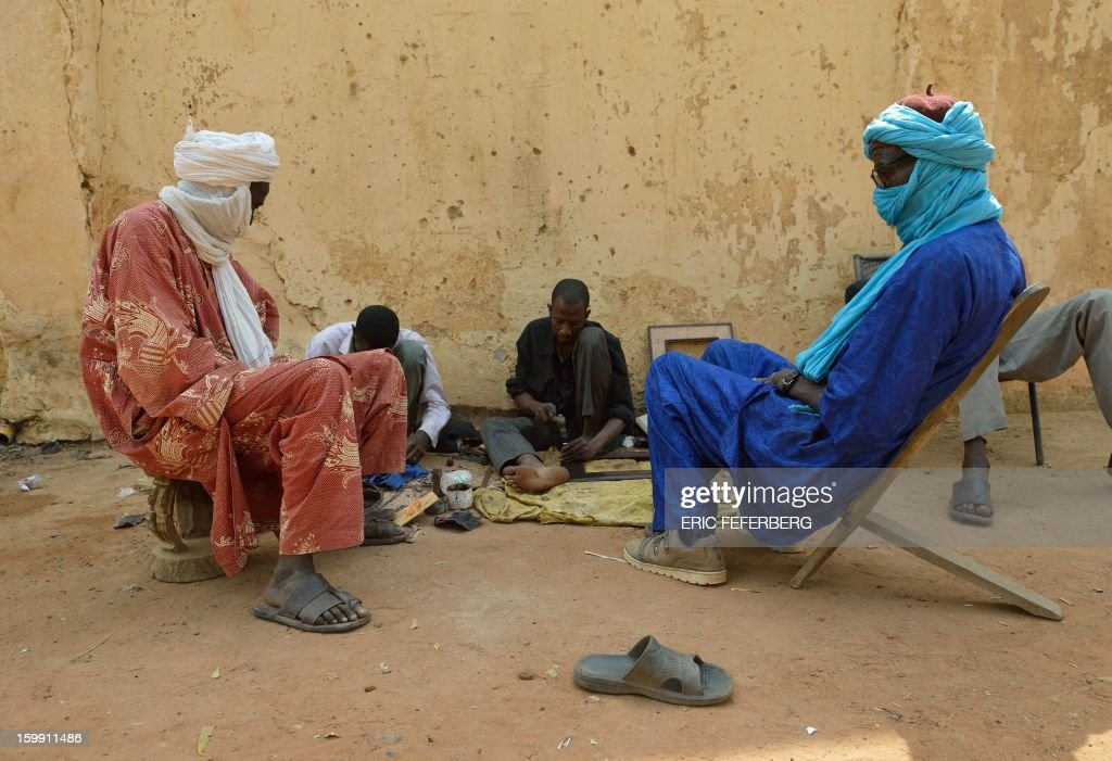 Tuareg men sit on January 22, 2013 in Segou, 270 kms north of Bamako. Since France began its military operation on January 11 in Mali, which lost over half of its territory to Islamists, amid rising fears that the vast northern half of the country could become a new Afghanistan-like haven for Al-Qaeda, Tuaregs and Malian Arabs, often assimilated with 'terrorists' by black Malians, fear for their safety. AFP PHOTO / ERIC FEFERBERG