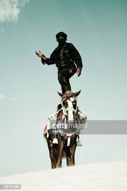 Tuareg Standing on Horse in Sand Dune