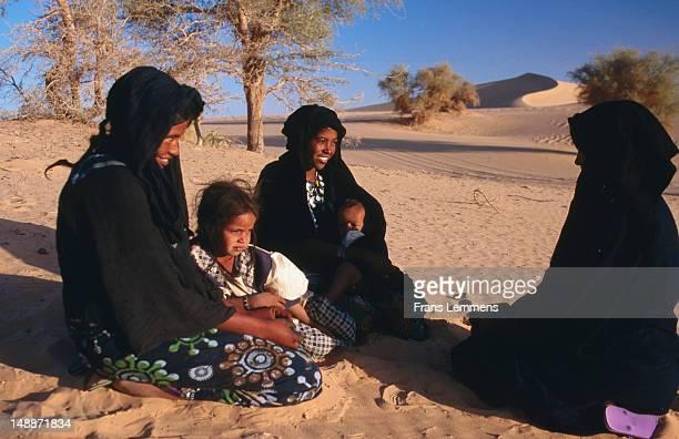 Tuareg women and children in sand dunes, Sahel region near Agadez.