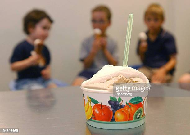 A tub of ice cream sits on the table while a group of children test the ice cream at Oddono's in south Kensington London Tuesday July 12 2005