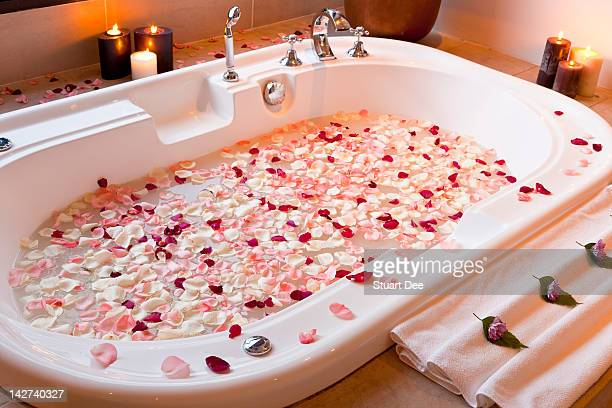 Tub with flower petals and candles