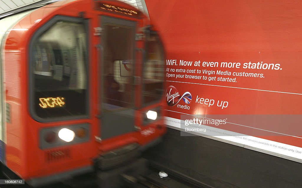 A tube train passes a sign promoting Virgin Media's WiFi service on London's Underground network at Liverpool Street station in London, U.K., on Wednesday, Feb. 6, 2013. Billionaire John Malone's Liberty Global Inc. agreed to acquire Virgin Media, Britain's second-largest pay-TV provider, in a $16 billion cash-and-stock transaction announced in the U.S. yesterday. Photographer: Chris Ratcliffe/Bloomberg via Getty Images