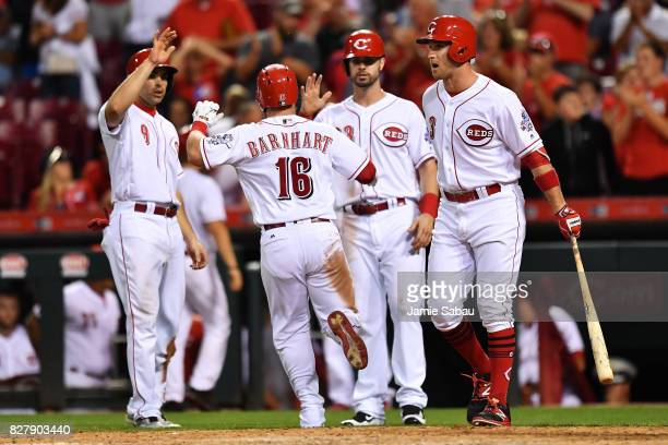 Tucker Barnhart of the Cincinnati Reds celebrates at home plate with Jose Peraza of the Cincinnati Reds and Jesse Winker of the Cincinnati Reds after...
