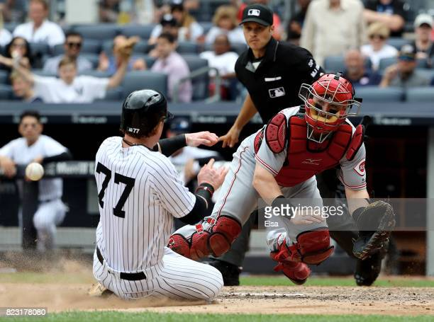 Tucker Barnhart of the Cincinnati Reds is unable to make the tag as Clint Frazier of the New York Yankees reaches home safely in the seventh inning...