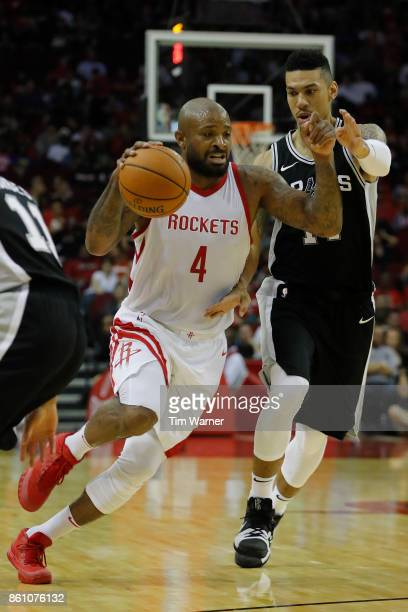 Tucker of the Houston Rockets drives to the basket defended by Danny Green of the San Antonio Spurs in the second half at Toyota Center on October 13...