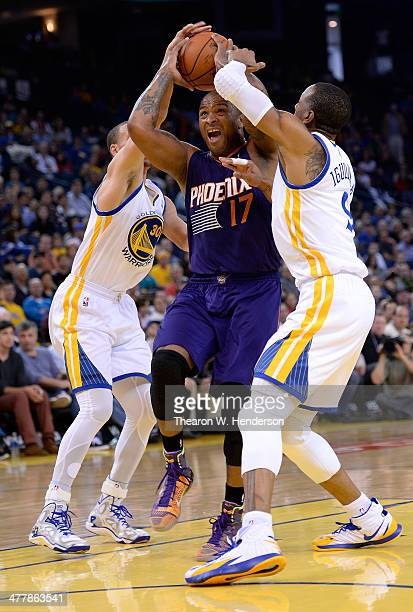 J Tucker of the Phoenix Suns drives on Andre Iguodala and Stephen Curry of the Golden State Warriors at ORACLE Arena on March 9 2014 in Oakland...