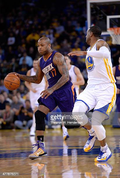 J Tucker of the Phoenix Suns drives on Andre Iguodala of the Golden State Warriors at ORACLE Arena on March 9 2014 in Oakland California NOTE TO USER...