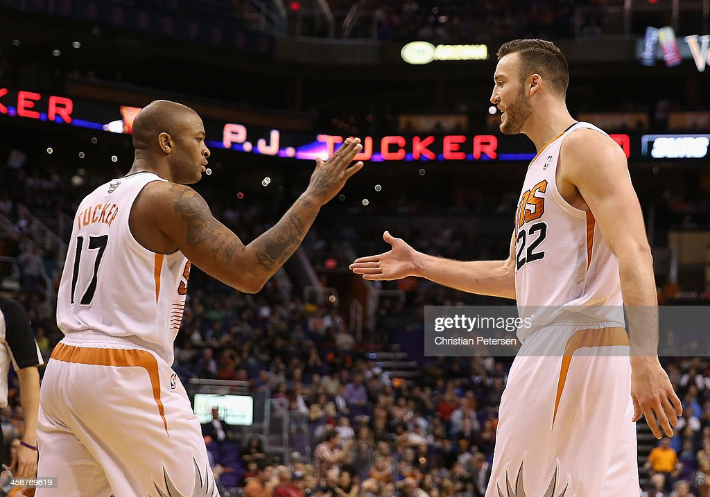 P.J. Tucker #17 of the Phoenix Suns high-fives Miles Plumlee #22 after scoring against the Dallas Mavericks during the first half of the NBA game at US Airways Center on December 21, 2013 in Phoenix, Arizona. The Suns defeated the Mavericks 123-108.