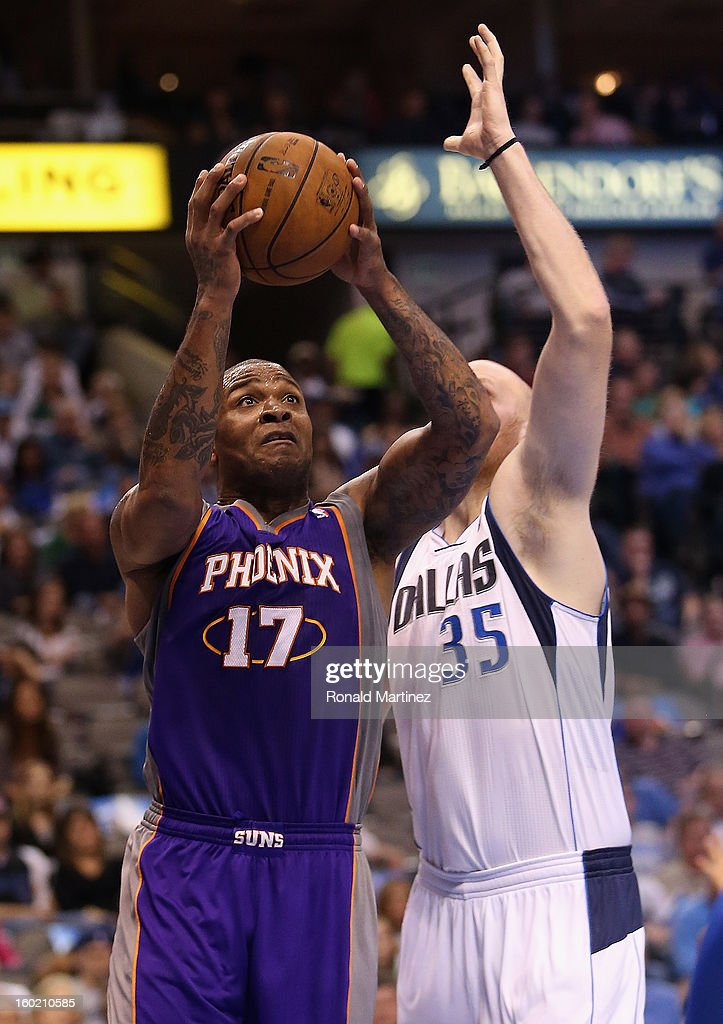 P.J. Tucker #17 of the Phoenix Suns takes a shot against Chris Kaman #35 of the Dallas Mavericks at American Airlines Center on January 27, 2013 in Dallas, Texas.