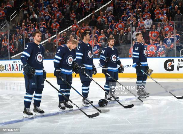 Tucker Poolman Andrew Copp Adam Lowry Josh Morrissey and Shawn Matthias of the Winnipeg Jets stand for the singing of the national anthem prior to...