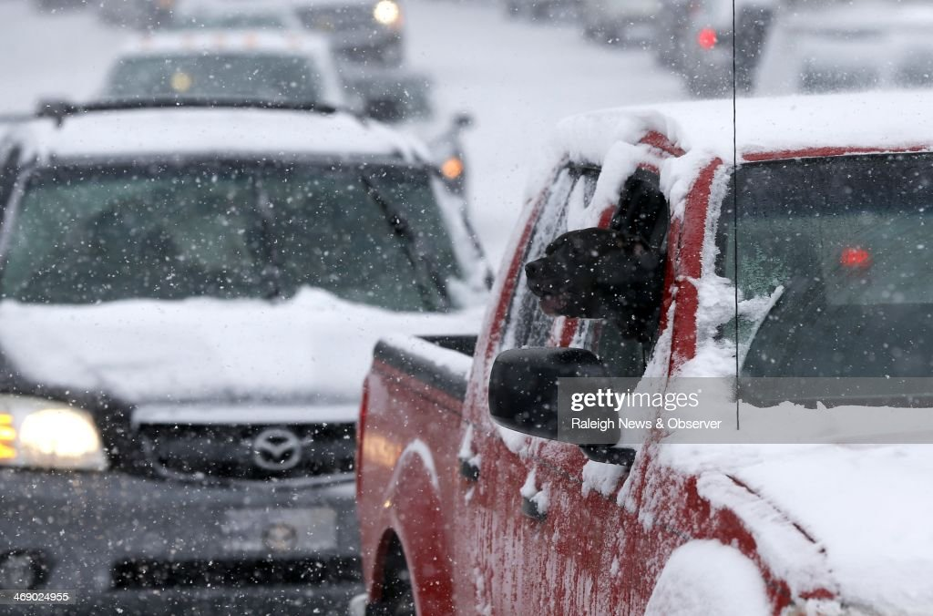 'Tuco' takes a look out as owner Troy Johnston sits stuck in traffic on South Boylan Avenue in the snow in Raleigh, N.C., Wednesday, Feb. 12, 2014.
