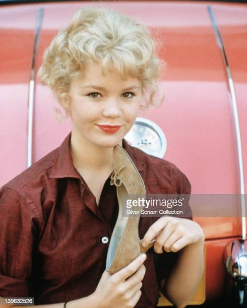 Tuesday Weld US actress wearing a dark red blouse holding a fawn suede stiletto shoe circa 1965