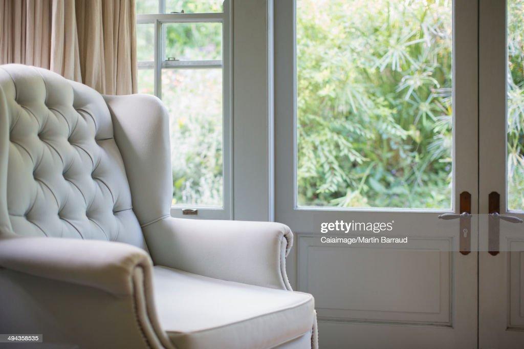 Tufted wingback chair near window