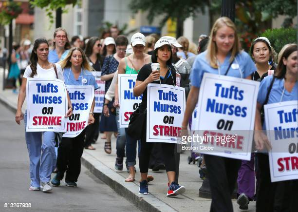 Tufts Medical Center nurses wear signs and form a picket line as they walk off their jobs and begin a strike in Boston on the morning of Jul 12 2017...