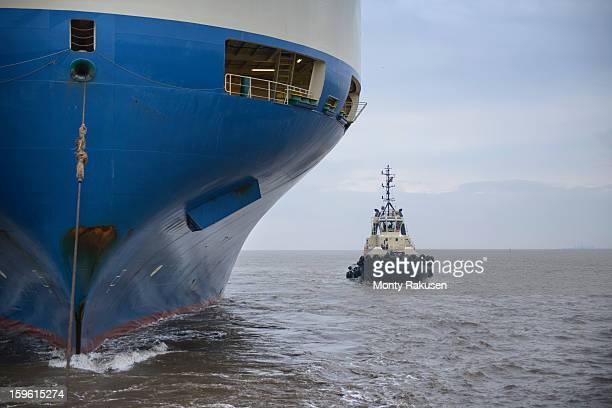 Tug alongside large ship out to sea