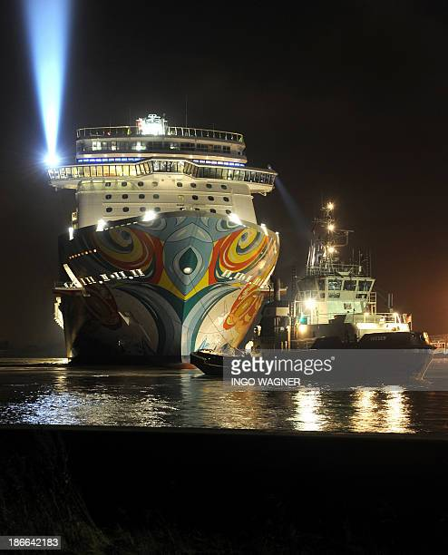 A tug boat pulls out cruise ship Norwegian Getaway from the shipyard of the Meyer wharf to a pier in Papenburg northern Germany on November 2 2013...
