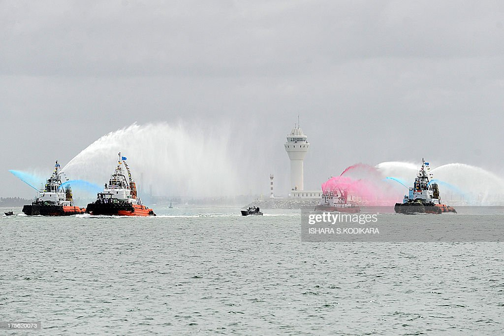 Tug boats at the Colombo harbour put on a water display as Sri Lanka President Mahinda Rajapakse travels by boat (2L) to ceremonially launch the Chinese-built Colombo International Container Terminal (CICT) in Colombo on August 5, 2013. Sri Lanka launched its biggest port with Chinese funding to turn Colombo into a strategic shipping hub along the world's most lucrative trading route. AFP PHOTO/ Ishara S. KODIKARA