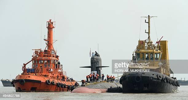 Tug boats escort the Scorpene submarine 'Kalvari' as it cruises into the Naval Dockyard in Mumbai on October 29 2015 'Kalvari' the first submarine of...