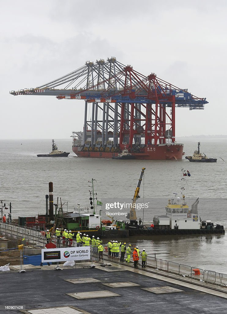 Tug boats position the Zhen Hua 26, a semi-submersible heavy load carrier operated by Shanghai Zhenhua Heavy Industry Co. Ltd. (ZPMC), as it delivers ship-to-shore container cranes to the new DP World Ltd. London Gateway shipping terminal in Stanford-le-Hope, U.K., on Friday, March 1, 2013. DP World, which operates more than 60 terminals in six continents, said it is on track to open new capacity in Santos in Brazil, Jebel Ali in the United Arab Emirates and London Gateway in the U.K. this year. Photographer: Chris Ratcliffe/Bloomberg via Getty Images