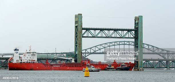 Tug boats press against the bow of the tanker Harbour Feature as the incoming tide presses it against the Sarah Mildred Long Bridge in the Piscataqua...