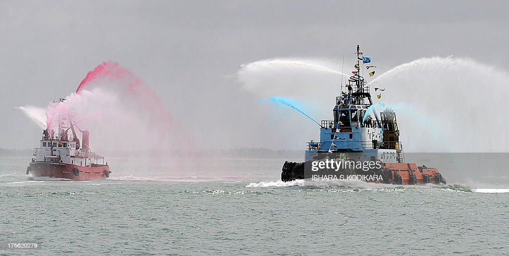 Tug boats put on a water display during the launch of the Chinese-built Colombo International Container Terminal (CICT) in the harbour of Colombo on August 5, 2013. Sri Lanka launched its biggest port with Chinese funding to turn Colombo into a strategic shipping hub along the world's most lucrative trading route. AFP PHOTO/ Ishara S. KODIKARA