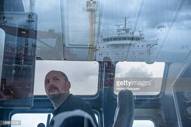 Tug captain looking into distance, with reflections of ship on glass