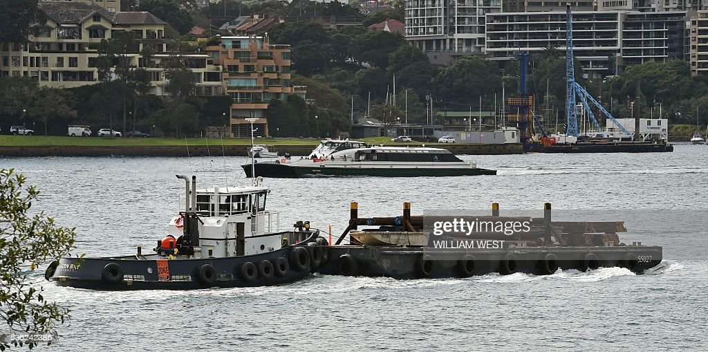 A tug pushes a barge on Sydney Harbour in Sydney on June 1, 2016 Australia's economy defied market forecasts with stronger-than-predicted expansion in January-March, driven by net exports and household spending, strengthening expectations interest rates will remain on hold for some months. Economic growth expanded by 1.1 percent in the first quarter for an annual year-on-year reading of 3.1 percent, the highest in recent years and far above economists' estimates of 0.8 percent and 2.9 percent. / AFP / William WEST