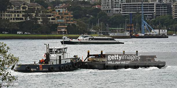 A tug pushes a barge on Sydney Harbour in Sydney on June 1 2016 Australia's economy defied market forecasts with strongerthanpredicted expansion in...