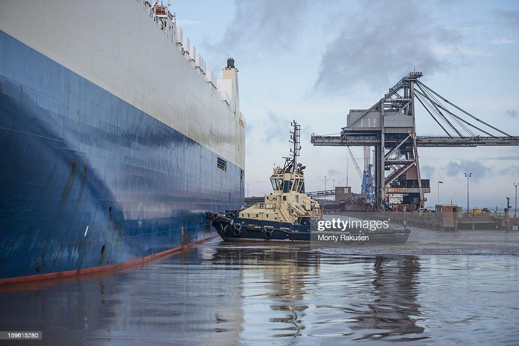Tug pushing ship in port