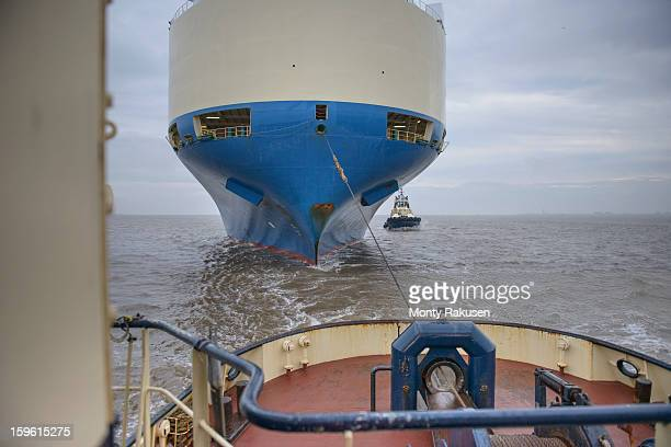 Tug towing car ship with rope out at sea