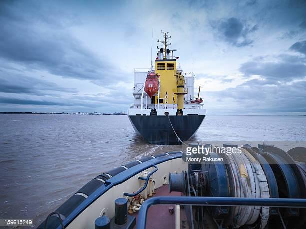 Tug towing ship out at sea