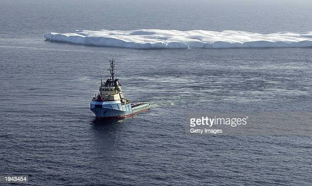 A tug tows an iceberg to safer waters and away from a possible collision with an oildrilling platform off the coast of Newfoundland April 21 2003 in...
