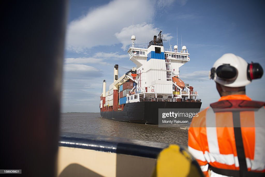 Tug worker wearing hard hat looking out towards container ship at sea