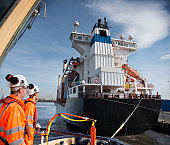 Tug workers on tug with container ship close by