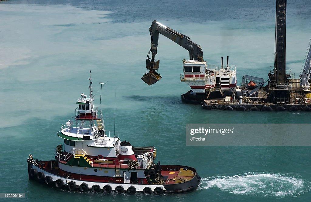 Tugboat and Dredge Dredging the Harbor