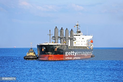 Tugboat assisting cargo ship : Stock Photo