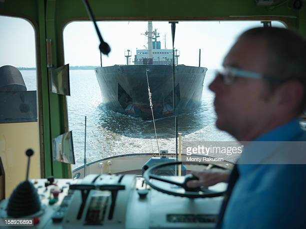 Tugboat captain in bridge towing ship at sea