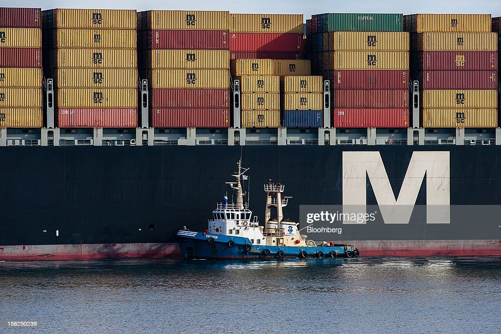 A tugboat positions the container ship MSC Renee for docking as it arrives at the open deep-water Port of Sines in Sines, Portugal, on Tuesday, Dec. 11, 2012. The Portuguese government is ready to implement additional measures in 2013 if there are slippages in meeting budget targets, the European Commission said. Photographer: Mario Proenca/Bloomberg via Getty Images