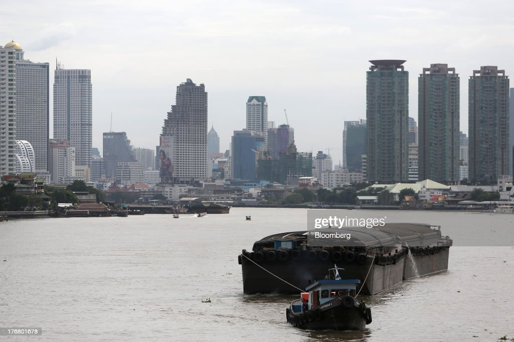A tugboat pulls a barge along the Chao Praya river in Bangkok, Thailand, on Sunday, Aug. 18, 2013. Thai economic growth slowed for a second quarter as exports cooled and local demand weakened, with rising household debt restricting the scope for monetary easing. Photographer: Dario Pignatelli/Bloomberg via Getty Images