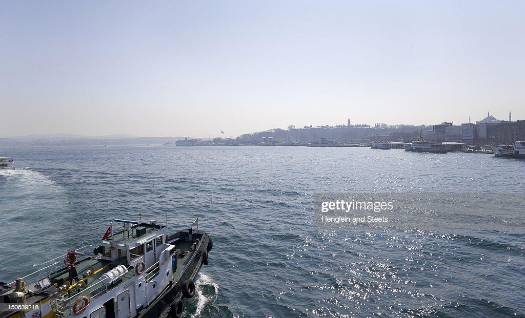 Tugboat sailing in urban bay : Stock Photo