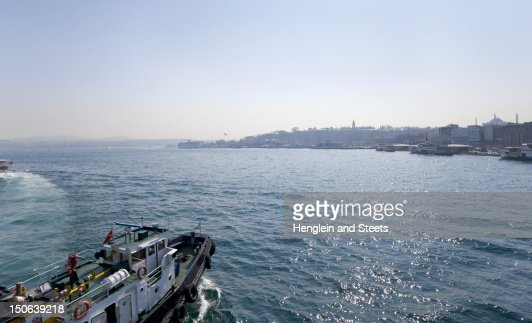 Tugboat sailing in urban bay : Stock Photo