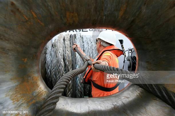Tugboat sailor feeding heavy ships mooring rope through ships bow